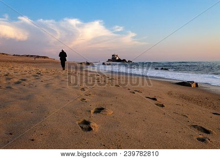 An Old Man Walks Along The Shoreline Towards A Chapel In The Background At The Beach.