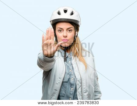 Young woman with bike helmet and earphones annoyed with bad attitude making stop sign with hand, saying no, expressing security, defense or restriction, maybe pushing