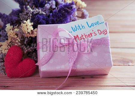 Happy Mother's Day Concept. Gift Box With Flower, Paper Tag With Love Mother's Day Text On Wooden Ta