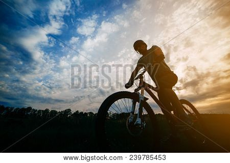 Sports, Tourism And Activity Concept. Silhouette Of A Cyclist In Helmet Riding A Bicycle Over Sunset