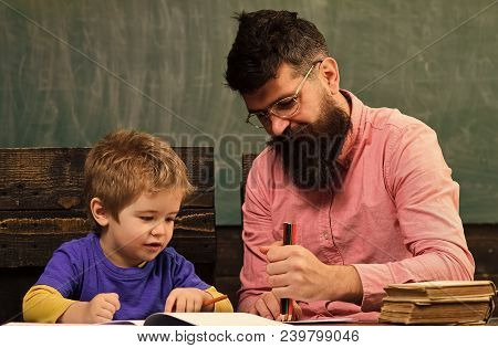 Pupil And Teacher Drawing In Copybook. Father And Son Having Fun Together. Preschool Education Conce