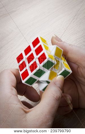 Color Cubical Puzzle In Female Hands On A Wooden Table, Kiev, Ukraine, 01/04/2018