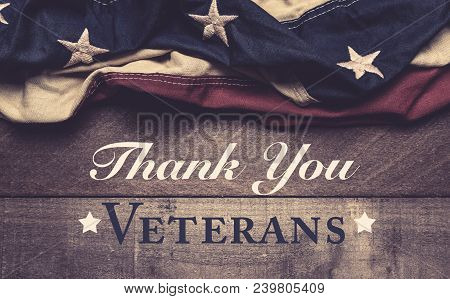 An American Flag Or Bunting On A Wooden Background With Veteran's Day Greeting