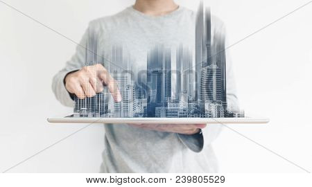 A Man Using Digital Tablet, And Modern Buildings Hologram. Real Estate Business And Building Technol