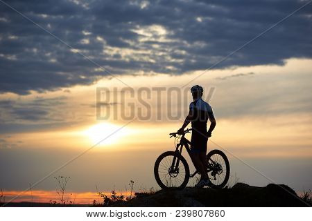 Back View Of Robust Cyclist Standing Near Bicycle And Observing Great View Of Amazing Sunset, Clouds