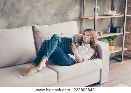 Serious Young Lady Is Studying, Lying On The Cozy Couch In Living Room At Home, So Nice Modern Inter