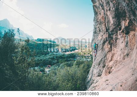 A Climber Climbs The Rock.