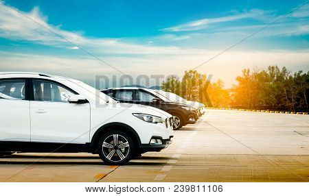 Luxury White And Black New Suv Car Parked On Concrete Parking Area At Factory With Blue Sky And Clou