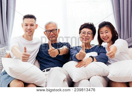 Asian Family With Adult Children And Senior Parents Giving Thumbs Up And Relaxing On A Sofa At Home