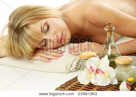Beautiful young woman enjoying massage at spa salon