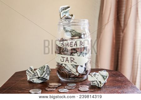 Swear jar to prevent swearing, filled with money