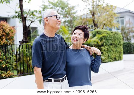 Happy Retired Senior Asian Couple Walking And Looking At Each Other With Romance In Outdoor Park And