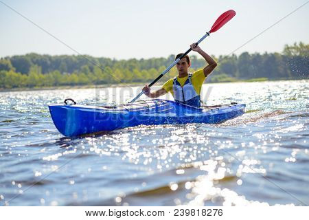 Young Professional Kayaker Paddling Kayak on the River under Bright Morning Sun. Sport and Active Lifestyle Concept