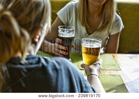 Beer. Friends Having A Round Of Drinks In A Pub. Women Are Drinking Beer And The Clink Glasses In A