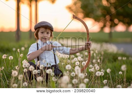 Portrait Of Child Playing With Bow And Arrows, Archery Shoots A Bow At The Target.