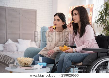 Sisters Friendship. Attentive Sister And Immobile Woman Eating Cheeps And Regarding Film