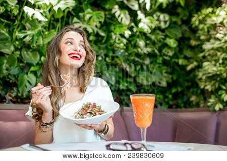 Young And Beautiful Woman Enjoying Heathy Salad Sitting At The Vegetarian Restaurant With Living Wal