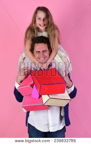 Daughter Sits On Dads Shoulders. Girl And Man With Cheerful Faces Hold Shopping Bags On Pink Backgro