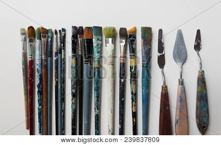 fine art, creativity and artistic tools concept - palette knives or painting spatulas and paintbrushes from top