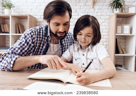 Bearded Father Helps Young Son To Do School Homework . Kid Writes In Copybook. Self Education Concep