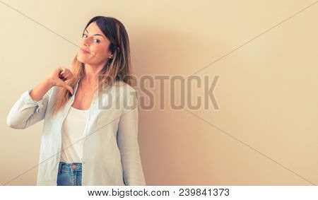 Vintage photo of a Beautiful woman against wall proud, excited and arrogant, pointing with victory face