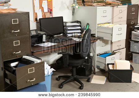 Messy office with piles of files and disorganized clutter.