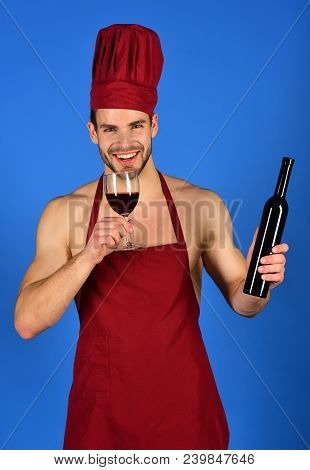 Beverage And Cookery Concept. Chef With Beard In Burgundy Hat And Apron Holds Bottle And Wineglass.