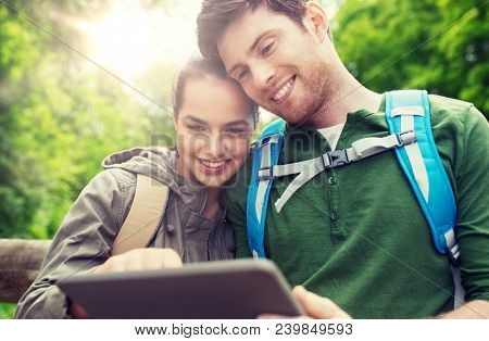 travel, hiking, backpacking, tourism and people concept - smiling couple with backpacks and tablet pc computer in nature