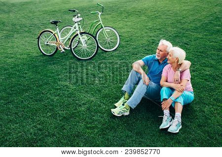 Cheerful Senior Couple Sits On The Grass, Enjoying The Rest After Riding Bicycles. Bicycles Stand Ne
