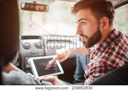 Handsome And Bearded Guy Is Holding A White Tablet And Pointing To The Screen. He Is Looking To His