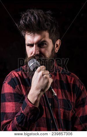 Musician, Singer Singing In Music Hall, Club. Musician With Beard And Mustache Lighted By Spotlight.