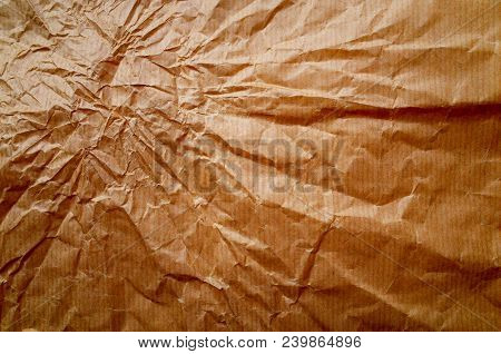 A Background Of Wrinkled Brown Wrapping Paper With Creases Radiating From The Top Left Corner. Proce