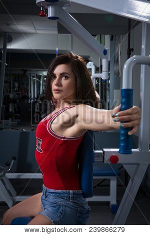 Sports Woman Doing Exercises On Power Training Apparatus In The Gym. In Stoke.the Young Girl Doing E