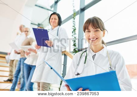 Young woman as doctor or nurse in medicine apprenticeship with team of doctors