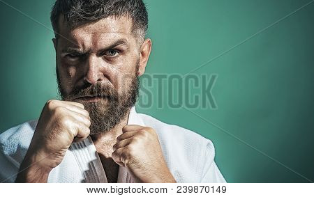 Karate Man In Kimono In Fighting Stance On Green Background. Portrait Of Fighter Performing Karate.