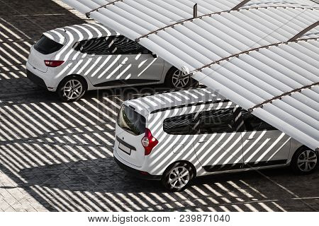 White Clean Cars On A Parking Lot In Sunny Summer Day. The Shadows From The Canopy Falling On Vehicl
