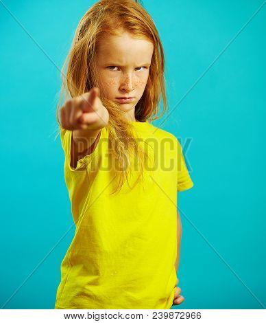 Shot of little girl with red hair accuses her finger at you, has a strict and scowled look, expresses bad mood, demonstrates severity and anger, portrait of frustrated child on blue isolated background. poster