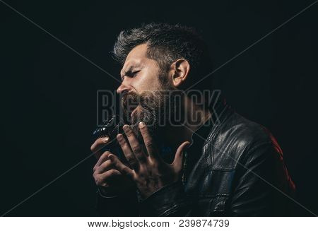 Life Style Concept - Handsome Man With Beard Wearing Black Leather Jacket Holding Microphone And Sin