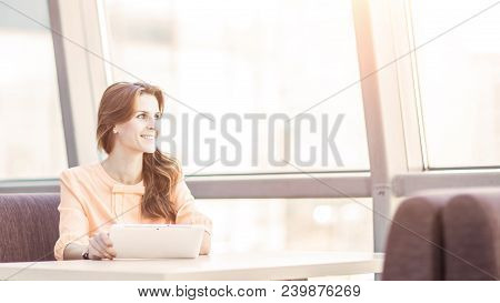 Business Woman With Digital Tablet Sitting At Desk In The Spacious Office. The Photo Has A Empty Spa