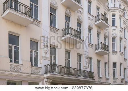 Frontage Old Restored House With White Windows Metal Balcony And Art Modeling In Pastel Colors