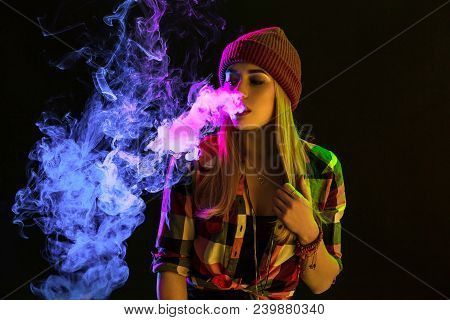Vaping Girl. Young Hipster Woman Vape E-cig On Studio On Black Background. Hip-hop Style. Close Up.