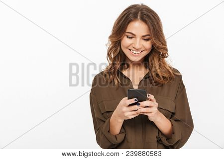 Portrait of a smiling young woman holding mobile phone isolated over white background