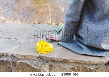 Young Woman Is Sitting On Border, Holding Bright Yellow Flowers, Lonliness Concept