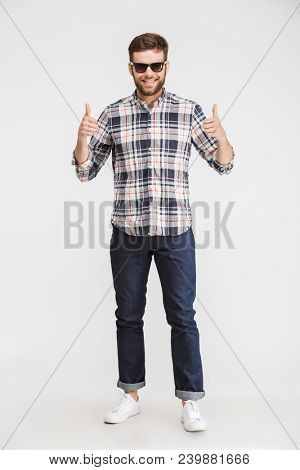 Full length portrait of a confident young man in plaid shirt and sunglasses showing thumbs up isolated over white background