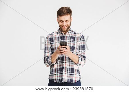 Portrait of a happy young man in plaid shirt holding mobile phone isolated over white background