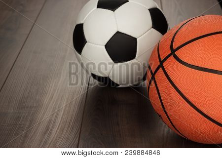 Soccer Ball And Basketball On The Brown Wooden Table