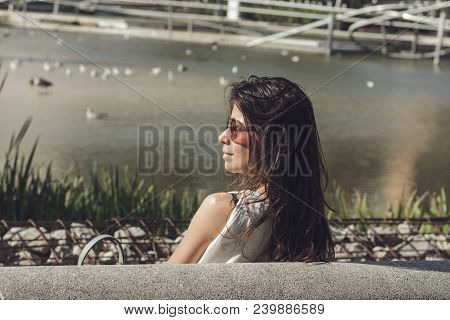 Portrait Of Young Woman In The Park. Woman With Sunglasses Sitting On The Park Bench. Young Woman In