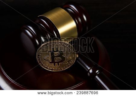 Auction Gavel And Bitcoin On A Wooden Desk, Close-up. Law Gavel And Golden Bitcoin Cryptocurrency Mo