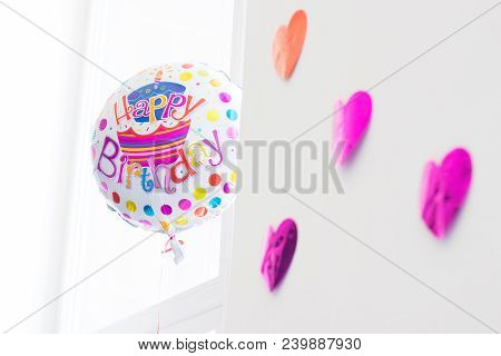 Happy Birthday Colorful Inflated Floating Baloon With Purple Hearts In White Bright Room With Window