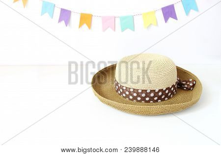 Straw Hat On White Table With Colorful Party Flags, Bunting Decoration. Greeting Card, Invitation Fo